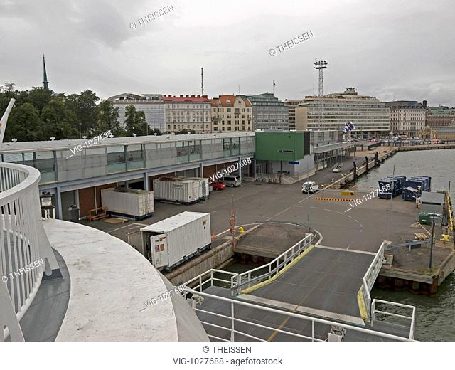 the harbour in Helsinki with containers and a gangway for tourists going on the ferry, the ferry starting to Tallin Estland over Baltic Sea
