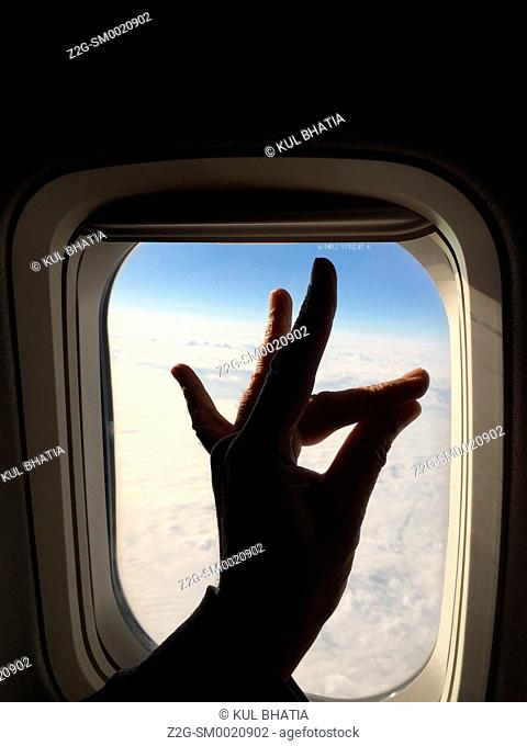 Hand gesture like the head of a deer held up against the plane window on board a commercial flight, Canada