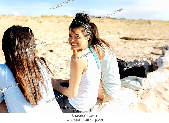 Happy female friends sitting on log on the beach