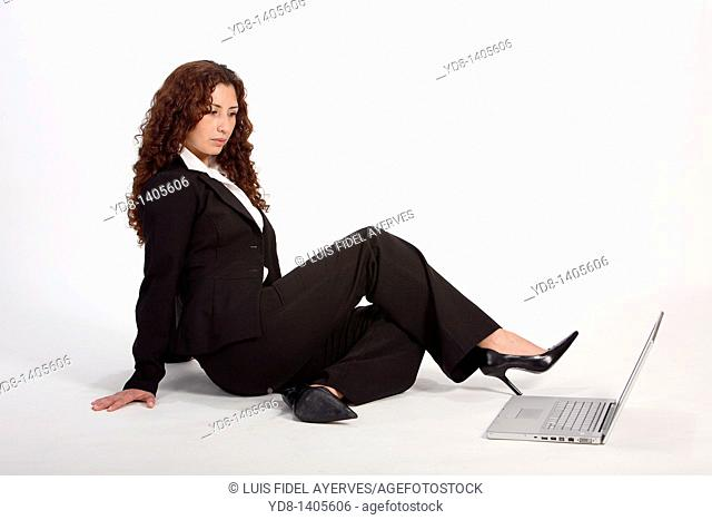 Young woman posing sitting in the studio as an executive with laptop