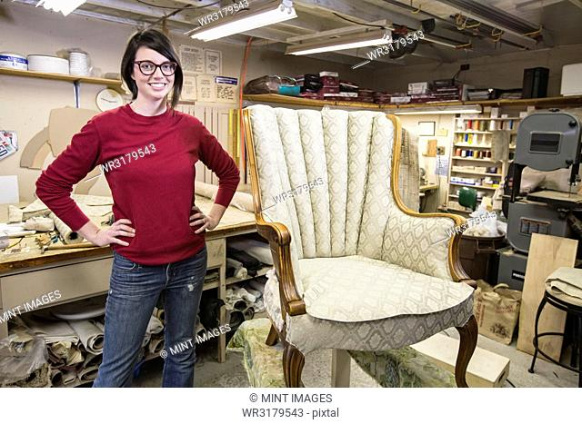 Portrait of a young Caucasian woman upholsterer and a chair she is working on