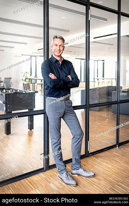 Businessman leaning on glass wall in his office, with arms crossed