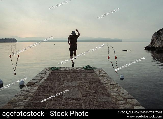 Man jumps from a jetty into the water