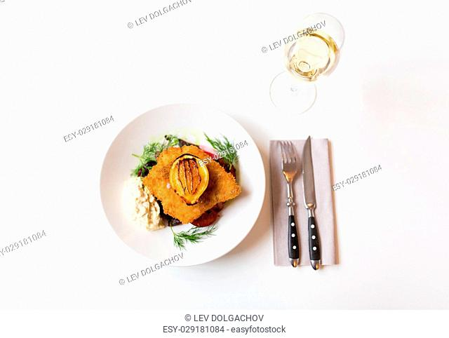 food, new nordic cuisine, dinner, culinary and cooking concept - fish salad with breaded fish fillet with tartar sauce and oven-baked beetroot tomato salad and...