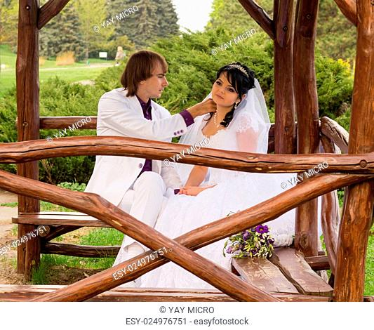 Couple love bride and groom posing sitting on wooden bench in