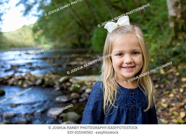 Young girl posing for a lifestyle portrait along the banks of the McKenzie River in Oregon