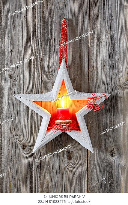 Natural Christmas decoration: A burning red candle in a white wooden star in front of a wooden wall. Switzerland