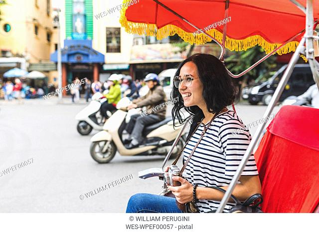 Vietnam, Hanoi, happy young woman on a riksha exploring the city