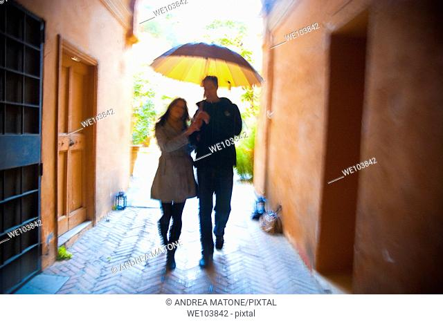 Couple with motion blur walking together with an umbrella under the rain in Rome Italy