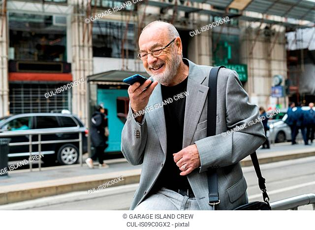 Businessman talking into smartphone on pavement, Milan, Lombardia, Italy