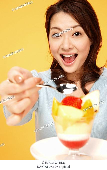Young woman eating bowl of fruit salad, portrait