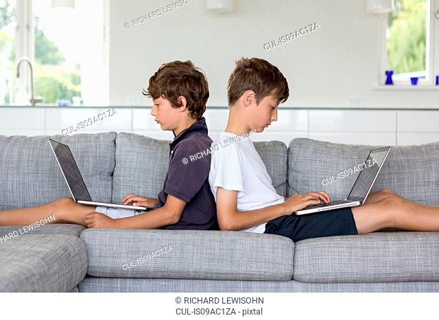 Brothers back to back on sofa using computers
