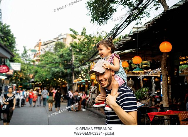 Thailand, Bangkok, portrait of smiling father and daughter on Khao San Road