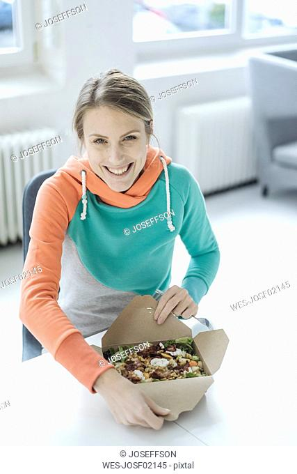 Portrait of laughing young woman having lunch in the office