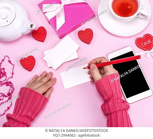 female hand holds a red wooden pencil and signs white paper business cards on a pink background, next to a smartphone with a black screen and a cup of tea