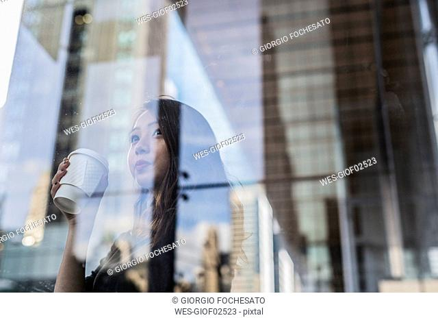 USA, New York City, Manhattan, young woman with coffee to go behind glass pane
