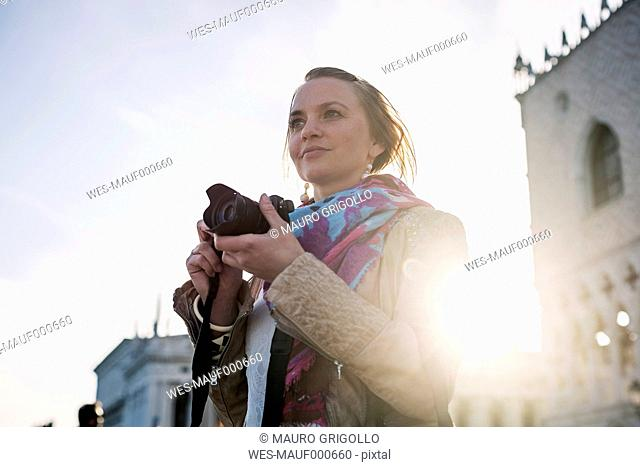 Italy, Venice, female Tourist taking pictures with camera, agsinst the sun