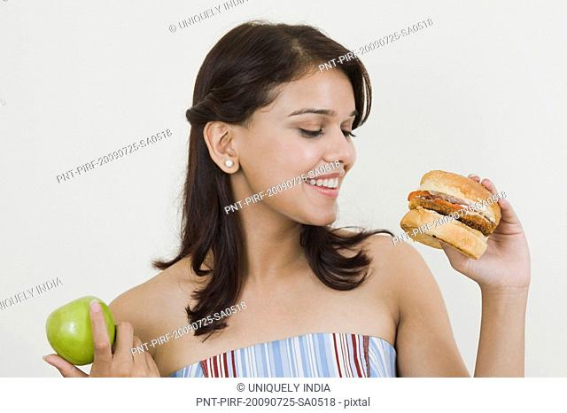 Woman holding a burger and a green apple