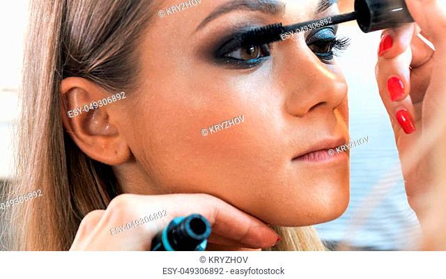 Macro of makeup artist painting model's eyes with mascara