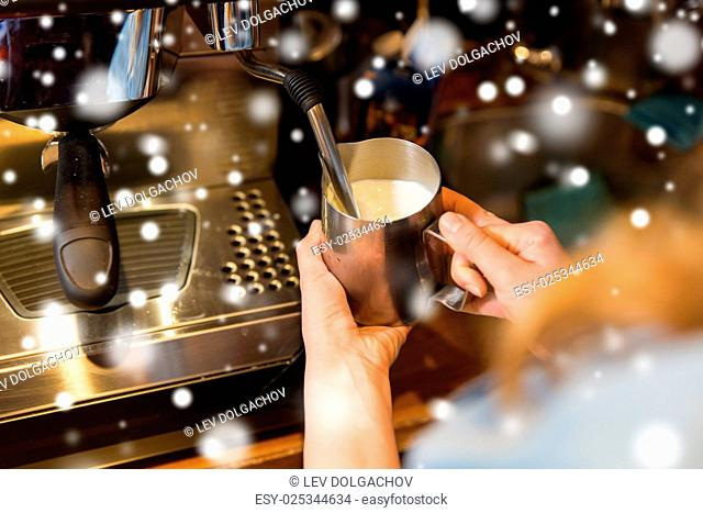 equipment, people and technology concept - close up of woman making coffee by machine at cafe bar or restaurant kitchen over snow