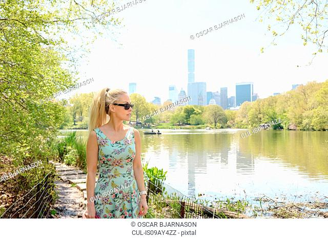 Female tourist strolling by boating lake in Central Park, New York, USA