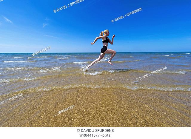 Woman jogging through the oceans waves