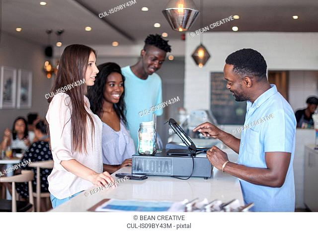 Customers paying at counter in ice cream parlour