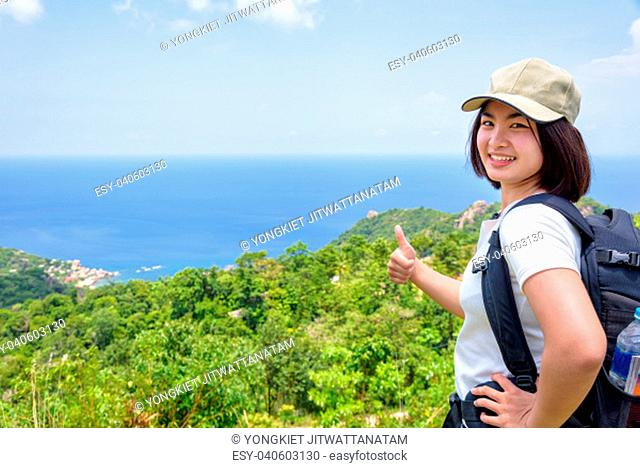 Women tourist with a backpack wear cap raise thumbs up for the beautiful nature landscape blue sea and sky from high scenic viewpoint at Koh Tao, Surat Thani
