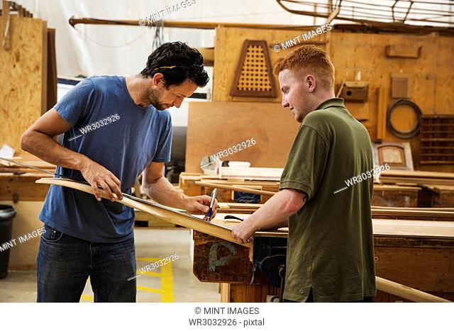 Two men standing at a workbench in a boat-builder's workshop, working on piece of wood