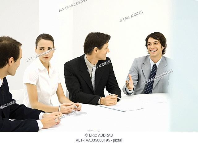 Business associates sitting around conference table, looking at each other, smiling