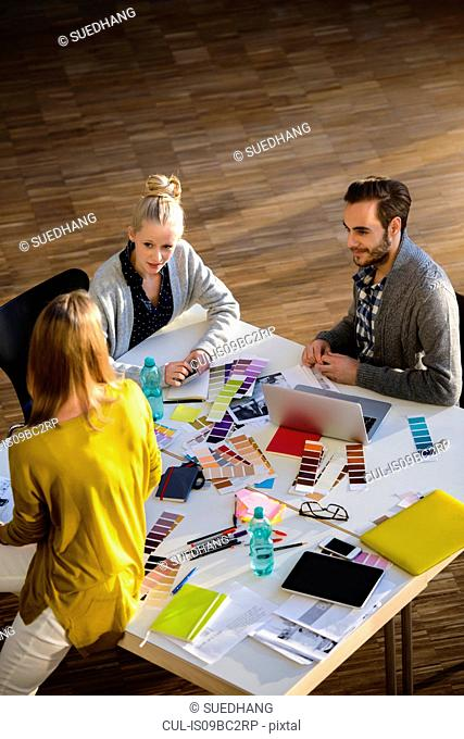 Male and female designers discussing colour swatches on design studio table