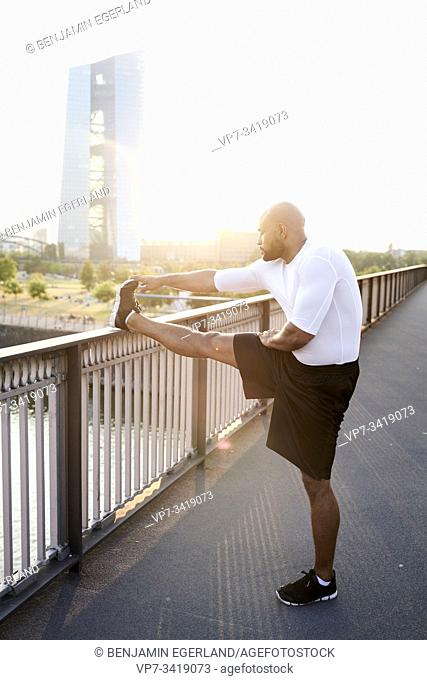 athletic man stretching next to European Central Bank Tower EZB in Frankfurt, Germany