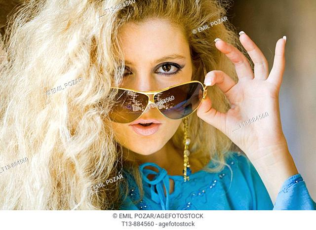 Looking over spectacles attractive Blonde woman portrait