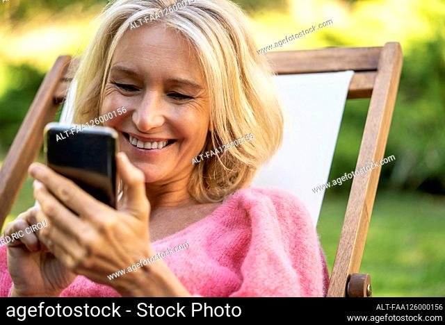 Close-up of smiling mature woman using smartphone while sitting on deckchair