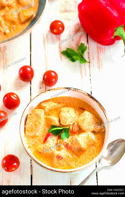 Delicious chicken stew with paprika in a bowl on a white wooden table. With fresh cherry tomatoes, red bell pepper and parsley