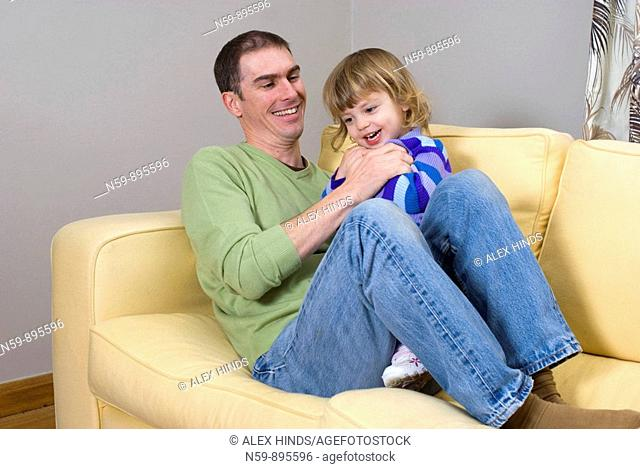 Young man playing with his daughter at home, tickling her