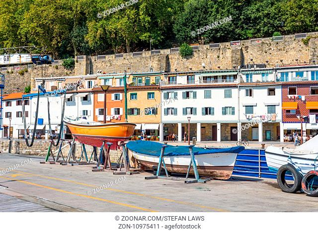 Picturesque houses in the old town, workshop with fishing boats and sport fishing boats for repair in the harbor of Donostia San Sebastian