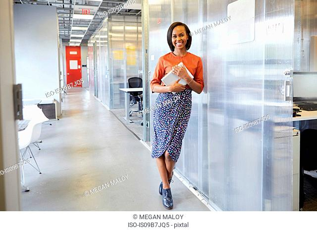 Portrait of businesswoman, leaning against office surround, holding digital tablet, smiling