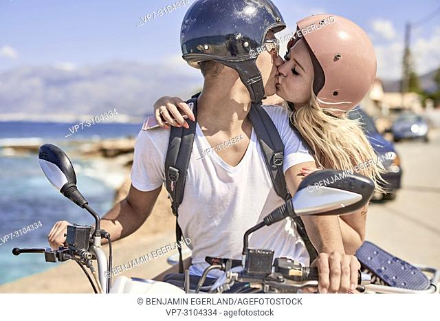 Greece, Crete, Chersonissos, couple driving quad next to coast, kissing, love, helmets, romantic, relationship, safety