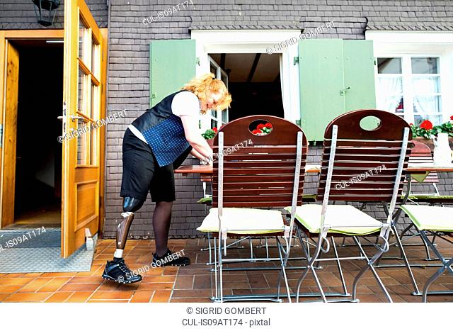 Mid adult woman with prosthetic leg, on patio