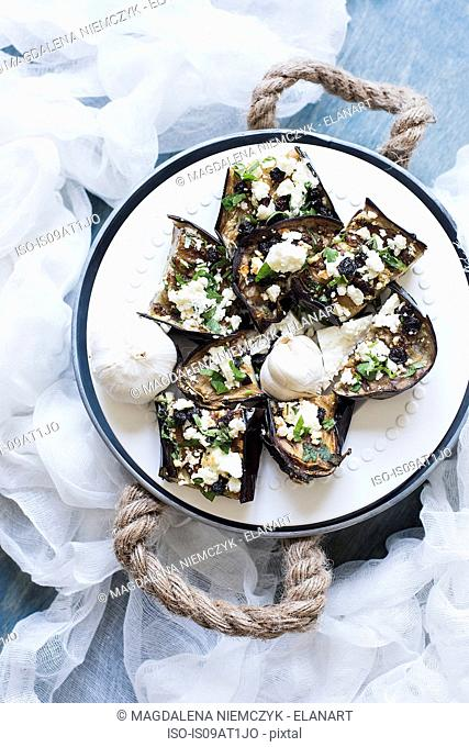 Still life plate of stuffed aubergines with ricotta and herb garnish