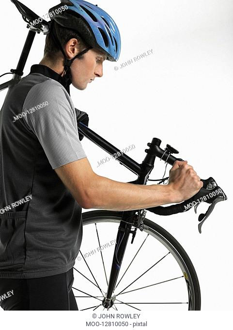 Male bicyclist carrying bicycle side view