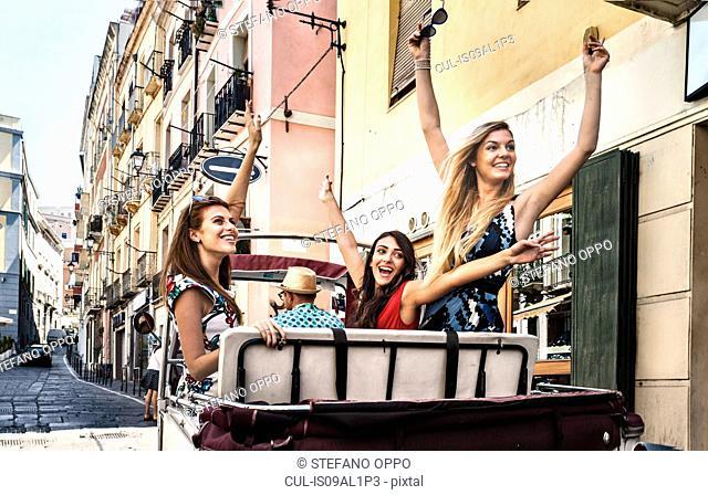 Three young women in open back seat of Italian taxi, Cagliari, Sardinia, Italy