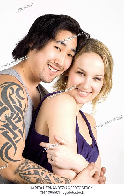 Smiling multicultural couple, asian & caucasian couple hugging  Both are looking into the camera, he has a long tatoo in the arm  White background