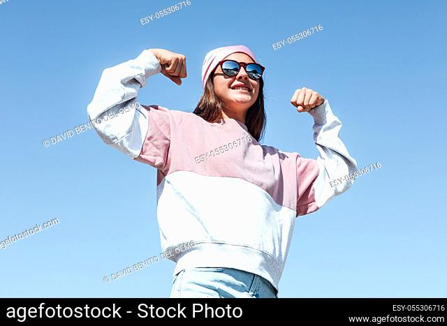 Girl woman with sunglasses and pink head scarf on her head, squeezes her arm as a sign of strength, on October 19, International Breast Cancer Day