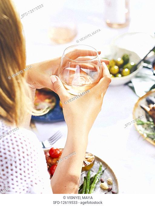 A woman with a glass of white sitting at a table laid with gilled dishes