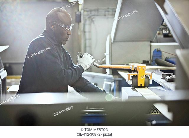 Worker operating machinery in steel factory