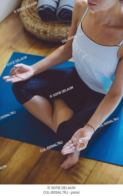 Cropped shot of mid adult woman sitting on bedroom floor in lotus position