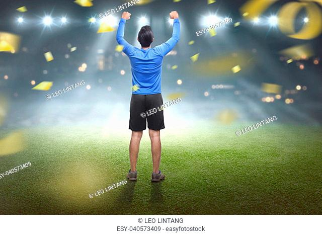 Back view of asian man celebrating his victory with confetti background