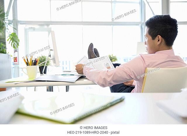 Businessman reviewing paperwork with feet up on desk